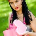 Beautiful brunette with heart shaped jewelry box — Stock Photo