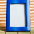 Blue wooden frame on bamboo mat — Stockfoto