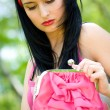Beautiful young brunette with pink purse — Stock Photo #10371021