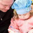Father teaching little daughter to write — Stock Photo #10371024