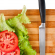 Red tomato slices, salad leaves and a knife — Stock Photo
