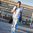 Mwith laptop walking along street — Stockfoto #10371133