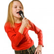 Pretty little girl singing in microphone isolated over white — Zdjęcie stockowe