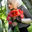 Stock Photo: Blonde with red tulips