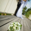 Bride and groom with flowers in front — Stock Photo
