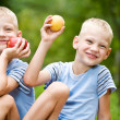 Two smiling twin brothers holding fruits — Stock Photo #10371326