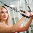 Royalty-Free Stock Photo: Pretty blond woman exercising on pulldown station