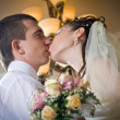 Beautiful young bride kissing groom in indoor setting — Stock Photo #10371337