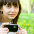 Young woman taking picture with digital camera — Stock Photo