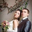 Beautiful young bride and groom in indoor setting — Stock Photo