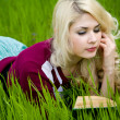 Beautiful young blond with book in summer park — Stock Photo