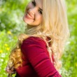 Smiling blond girl over green grass — Stock fotografie #10371597