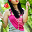 Sexy brunette with red tulip — Stockfoto