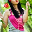 Sexy brunette with red tulip - Stock Photo
