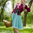 Beautiful young blond with basket in summer park — Foto Stock