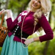 Beautiful young blond with basket in summer park — Stock Photo #10371614