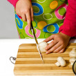 Girl wearing apron slicing mushrooms — Stockfoto