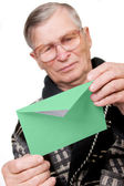 Elderly man opening letter envelope — Stock Photo