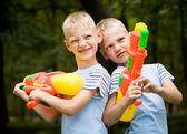 Dos hermanos gemelos con pistolas de agua sonriendo — Foto de Stock