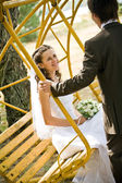 Groom rocking bride on swing — Stockfoto