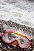 Potápěčská maska na štěrkové mořského pobřeží — Stock fotografie