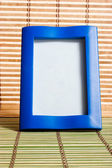 Blue wooden frame on bamboo mat — Stock Photo