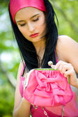 Beautiful young brunette with pink purse — Stock Photo