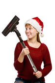 Smiling teen girl in santa hat with vacuum cleaner broom — Stock Photo