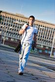 Man met laptop wandelen langs de straat — Stockfoto