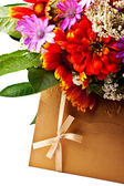 Flowers and golden colored envelope — Stock Photo
