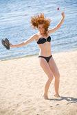 Jovem mulher pulando na praia — Foto Stock