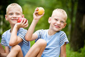 Two smiling twin brothers holding fruits — Stock Photo