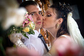 Beautiful young bride kissing groom — Stock Photo