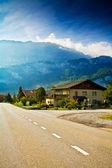 Körbanan löper över små alpina byn — Stockfoto