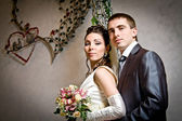 Beautiful young bride and groom in indoor setting — Stok fotoğraf