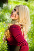 Smiling blond girl over green grass — Stok fotoğraf