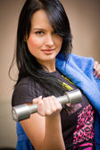 Young smiling woman with a dumbbell — Stock Photo