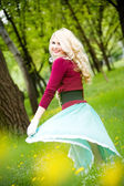 Beautiful young blond wearing long skirt in summer park — Stock Photo