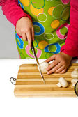 Girl wearing apron slicing mushrooms — Stock Photo