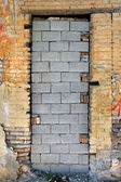 Bricked up door and chipped brick wall texture — Stock Photo