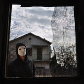 Hooded figure threaded window — Stock Photo