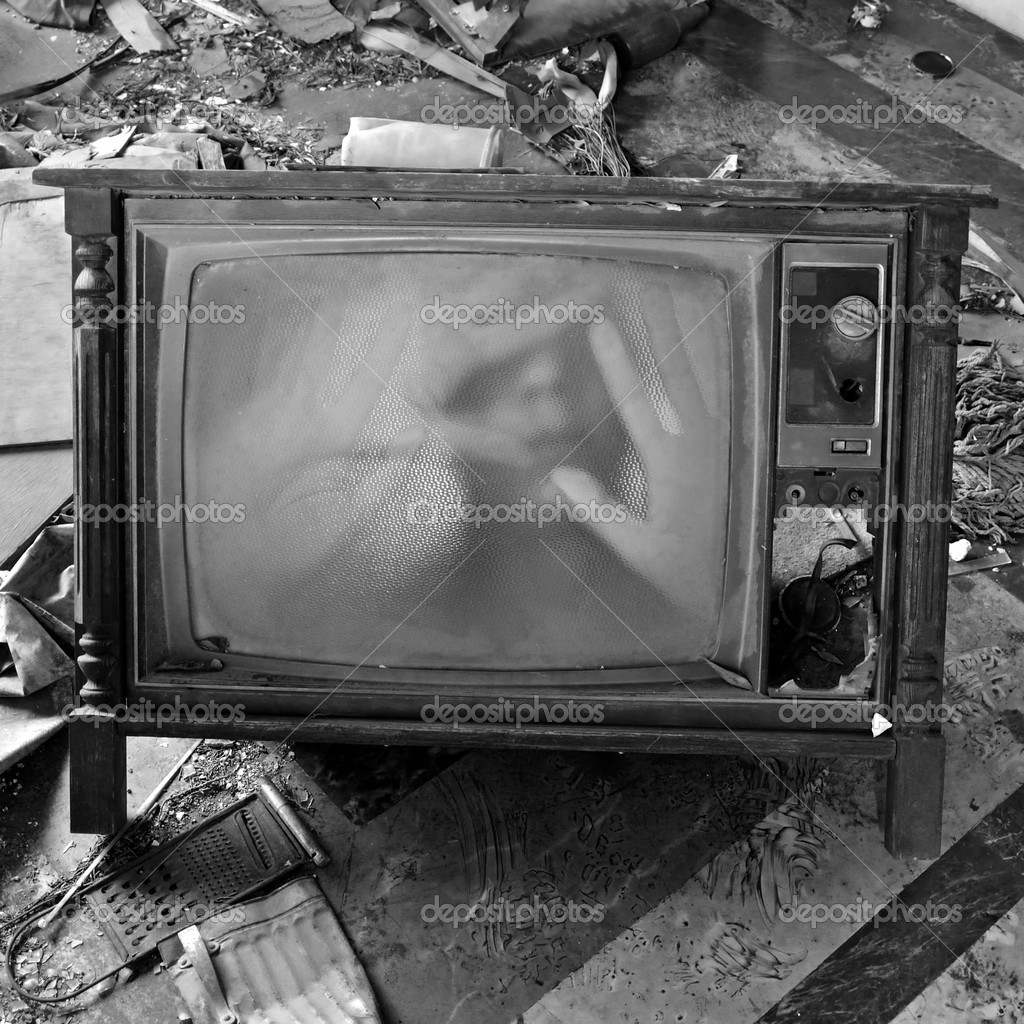 A ghostly figure appears on the flickering screen of an old tv set. Haunted house. — Stock Photo #9539435