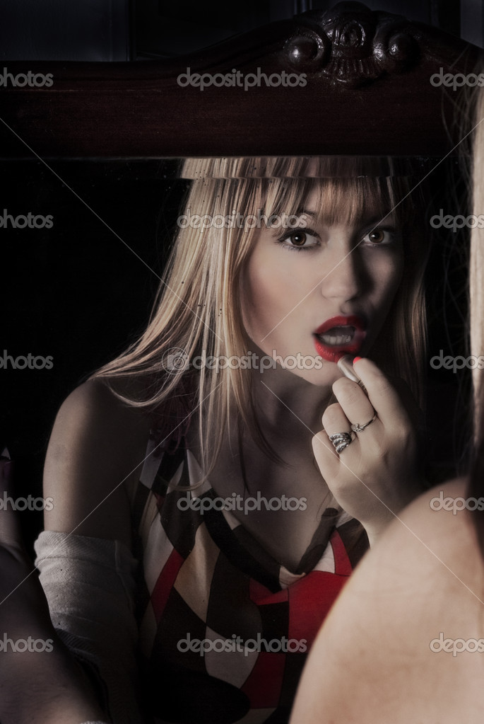 Sexy blond in front of mirror putting red lipstick — Stock Photo #10352049