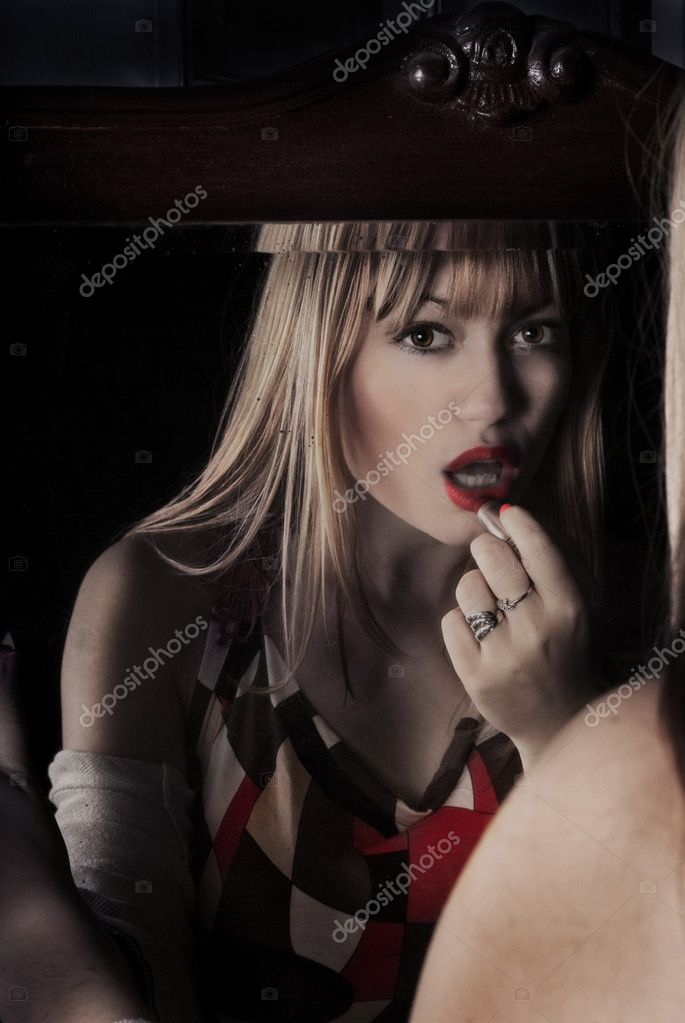 Sexy blond in front of mirror putting red lipstick — Photo #10352049