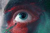 Mâle yeux bleus lumineux avec de la peinture de guerre — Photo