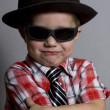 The boy in a hat and black glasses on a gray background - Stock Photo
