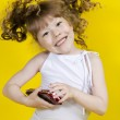 Little girl playing handheld portable game console — Stock Photo #8773485