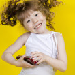 Little girl playing handheld portable game console — Stock Photo