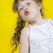 Cheerful girl dances on a yellow background — Stock Photo #8773527