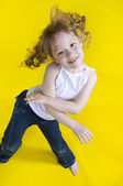 Cheerful girl dances on a yellow background — Stock Photo